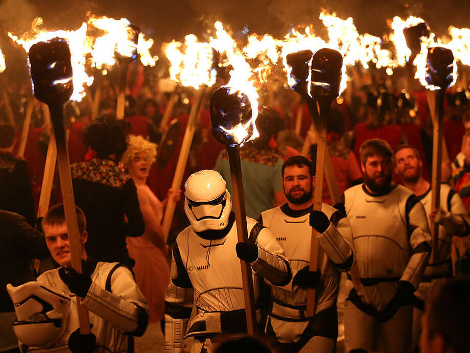 People dressed as Storm Troopers from the Star Wars films carry flaming torches during the Up Helly Aa Viking festival in Lerwick on the Shetland Isles, Scotland, Tuesday Jan. 26, 2016. Originating in the 1880's, the festival celebrates Shetland's Norse heritage and sees a 'Viking longship' dragged through the streets of Lerwick, led by a horde of people dressed as Vikings before being set alight. (Andrew Milligan/PA via AP) UNITED KINGDOM OUT NO SALES NO ARCHIVE