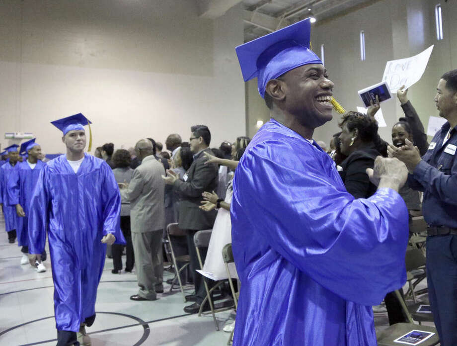 In this photo taken Dec. 12, 2014 shows inmates, in caps and gowns in the Prison Entrepreneurship Program marching toward the stage for graduation ceremonies, at the Cleveland Correctional Facility in Cleveland, Texas. The Prison Entrepreneurship Program, or PEP, is based on a philosophy that making inmates like Chavez business savvy will reduce the likelihood that they'll end up back in prison. It emphasizes reforming behavior while also working on a broader goal of reducing the prison population. (AP Photo/Pat Sullivan)