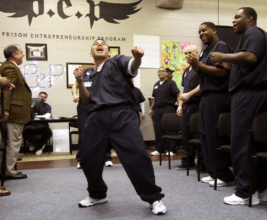 In this photo taken Dec. 12, 2014, prison inmate Nicholas Paz, center, dances down a a line of his classmates in the Prison Entrepreneurship Program, or PEP, right, and program sponsors, in Cleveland, Texas. The rigorous program teaches inmates how to finance a business, how to market their products and how to sell themselves and their stories. PEP's graduates have a recidivism rate of under 7 percent compared to 23 percent of the overall population in Texas. (AP Photo/Pat Sullivan)