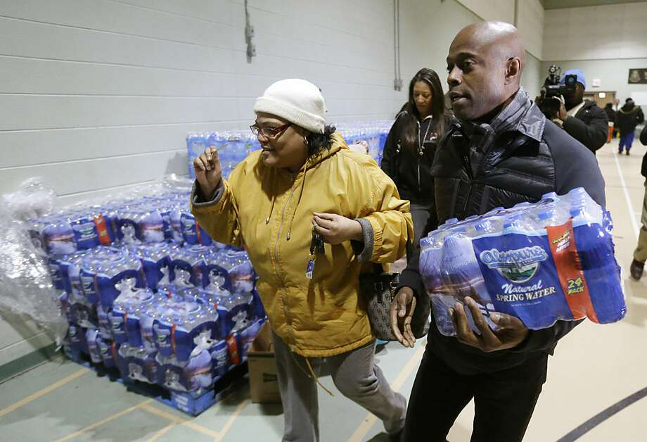 R&B singer Kem helps Mwamini Wallace carry bottled water to her vehicle in Flint, Mich., Tuesday, Jan. 26, 2016. Kem donated $10,000 to the Salvation Army to aid efforts to provide bottled water to residents in the city where drinking water has been contaminated by lead. (AP Photo/Carlos Osorio)