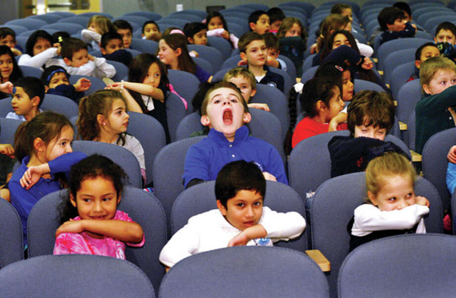 Hour photo / Erik Trautmann Rogers International School first and second graders including Ben Gragg, center, practice coughing and sneezing into their sleeve as Stamford's mayor David Martin visits the school to help kick off the district's increased efforts to prevent the flu and promote student wellness. Martin helped kick off the Clean Fins for all Terrapins poster contest, which the school is using to help promote respiratory etiquette and frequent hand washing with an assembly for 1st and 2nd grade students for the launch event Tuesday. / (C)2013, The Hour Newspapers, all rights reserved