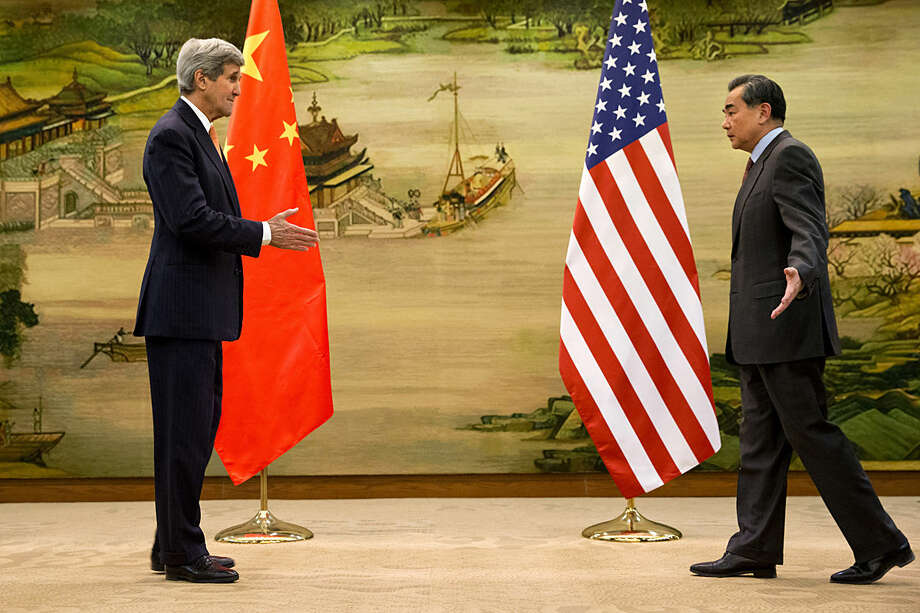 U.S. Secretary of State John Kerry, left, and Chinese Foreign Minister Wang Yi approach to shake hands after attending a news conference at the Ministry of Foreign Affairs in Beijing, Wednesday, Jan. 27, 2016. Kerry is on the final leg in his latest round-the-world diplomatic mission. (AP Photo/Jacquelyn Martin, Pool)
