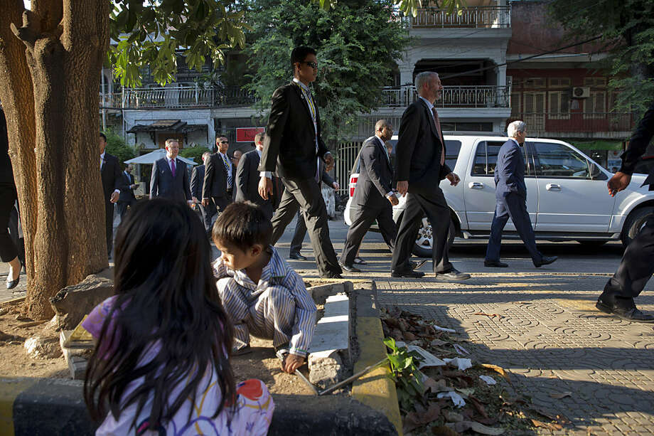 Children play on Street 240 as U.S. Secretary of State John Kerry, right, walks by while souvenir shopping in Phnom Penh, Cambodia, Tuesday, Jan. 26, 2016. Kerry is in Cambodia on the fourth leg of his latest round-the-world diplomatic mission, which will also take him to China. (AP Photo/Jacquelyn Martin, Pool)