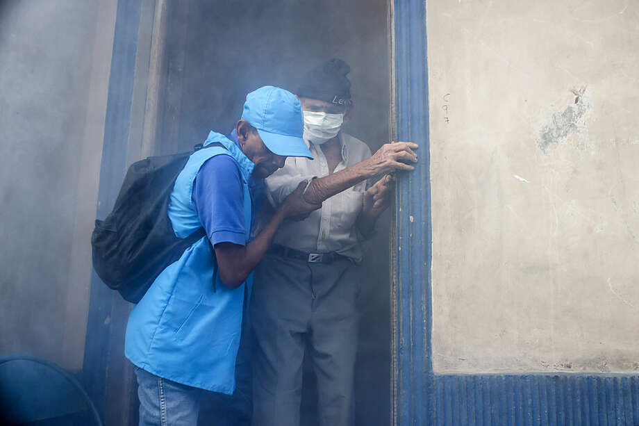 A city worker helps homebound Simon Jose Valentin, 94, leave his home while it is fumigated to combat the Aedes Aegypti mosquitoes that transmit the Zika virus, at the San Judas Community in San Salvador, El Salvador, Tuesday, Jan. 26, 2016. Worries about the rapid spread of Zika through the hemisphere has prompted officials in El Salvador, Colombia and Brazil to suggest women stop getting pregnant until the crisis has passed. (AP Photo/Salvador Melendez)