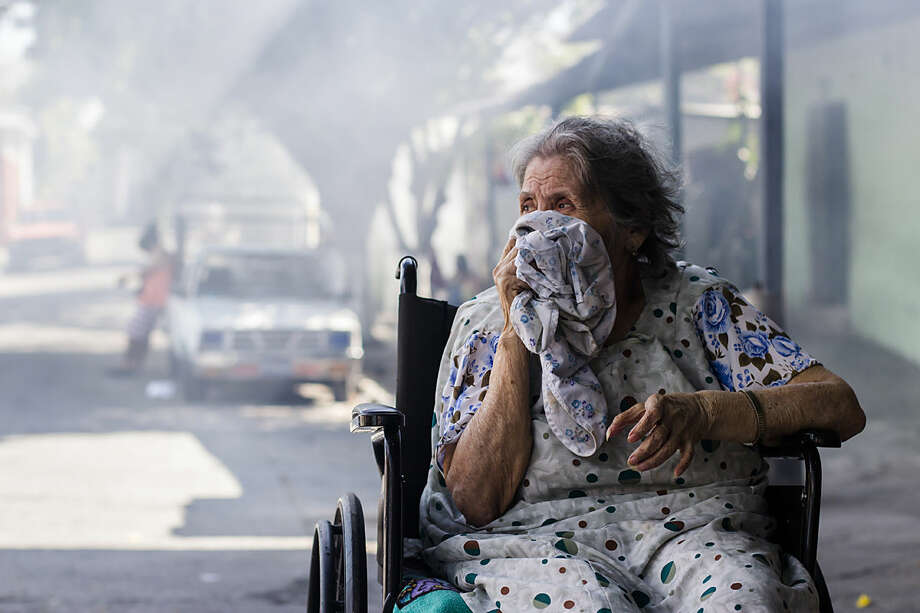 Carmen Chicas Mejia, 82, covers her mouth and nose while city workers fumigate her home to combat the Aedes Aegypti mosquitoes that transmit the Zika virus, at the San Judas Community in San Salvador, El Salvador, Tuesday, Jan. 26, 2016. Worries about the rapid spread of Zika through the hemisphere has prompted officials in El Salvador, Colombia and Brazil to suggest women stop getting pregnant until the crisis has passed. (AP Photo/Salvador Melendez)