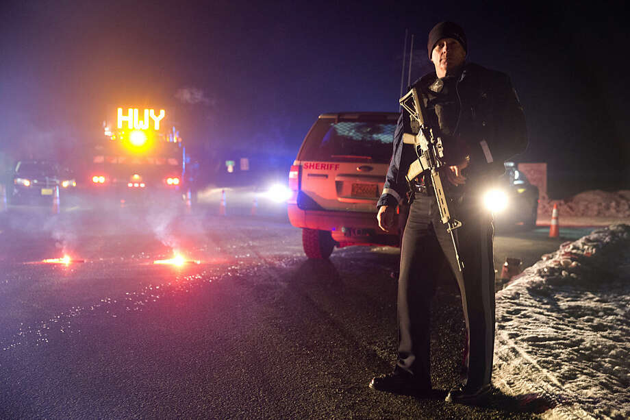 Sgt. Tom Hutchison stands in front of an Oregon State Police roadblock on Highway 395 on Tuesday, Jan. 26, 2016 between John Day and Burns, Ore. The FBI on Tuesday arrested the leaders of an armed group that has occupied a federal wildlife refuge in eastern Oregon for the past three weeks. (Dave Killen/The Oregonian via AP) MAGS OUT; TV OUT; NO LOCAL INTERNET; THE MERCURY OUT; WILLAMETTE WEEK OUT; PAMPLIN MEDIA GROUP OUT; MANDATORY CREDIT