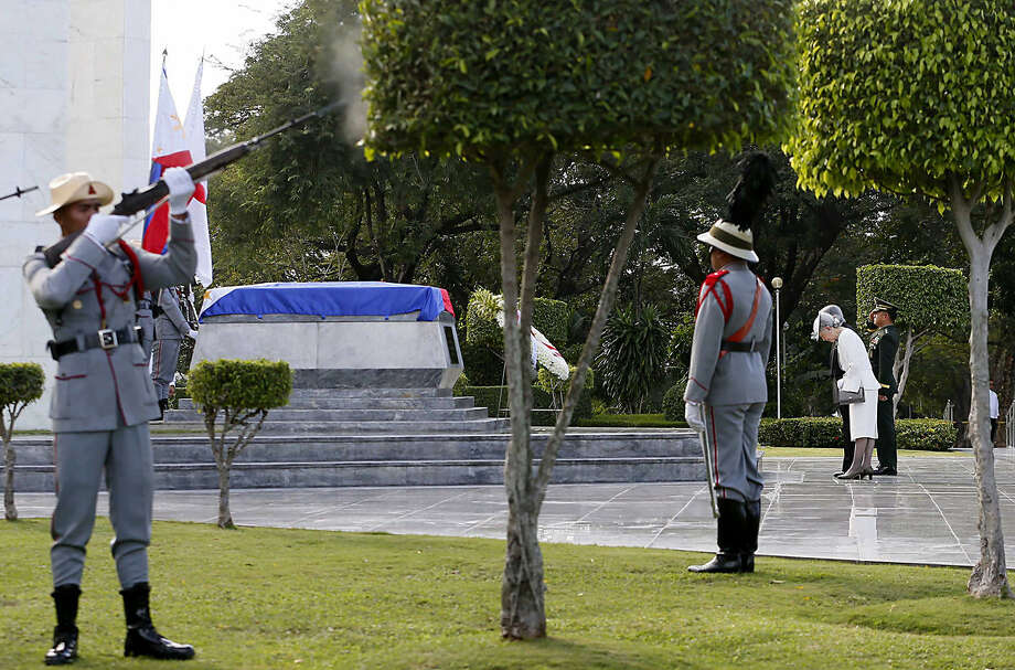 Japan's Emperor Akihito and Empress Michiko bow before the tomb of the unknown soldier as a soldier fires a salute during a wreath laying ceremony at the Heroes' Cemetery Wednesday, Jan. 27, 2016 in suburban Taguig city, east of Manila, Philippines. The 82-year-old Akihito pays his respects at memorials for both the Philippine and the Japanese war dead during his state visit. (AP Photo/Bullit Marquez)
