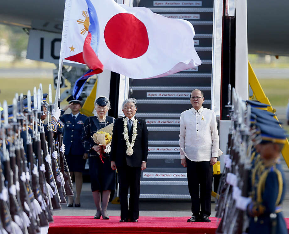 Japan's Emperor Akihito, center, Empress Michiko, left, and Philippine President Benigno Aquino stand at attention as the national anthems are played upon their arrival Tuesday, Jan. 26, 2016 in suburban Pasay city, south of Manila, Philippines. The 82-year-old Akihito will pay his respects at memorials for both the Philippine and the Japanese war dead during a five-day state visit. (AP Photo/Bullit Marquez)