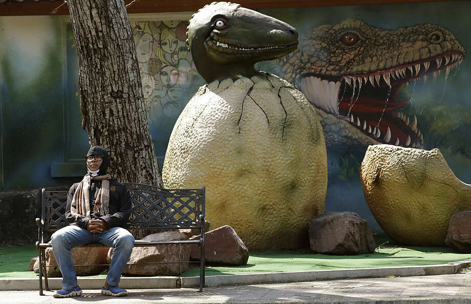 A Thai visitor wearing a scarf and a jacket sits on a bench at Dusit Zoo in Bangkok, Thailand, Tuesday, Jan. 26, 2016. January is the most wintry season for much of Asia, but few people were prepared for the sudden drop in temperatures that sent them scurrying this past weekend for coats and scarves. In the Thai capital Bangkok, where temperatures hit an unseasonably high 34 degrees C (93 F) this past Saturday, only to bottom out to a low of 15 degrees C (59 F) on Monday. (AP Photo/Sakchai Lalit)