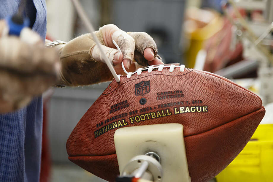 Donna Conley laces an official ball for the NFL Super Bowl 50 football game at the Wilson Sporting Goods Co. in Ada, Ohio, Tuesday, Jan. 26, 2016. The Denver Broncos will play the Carolina Panthers in the Super Bowl on Feb. 7 in Santa Clara, Calif. (AP Photo/Rick Osentoski)