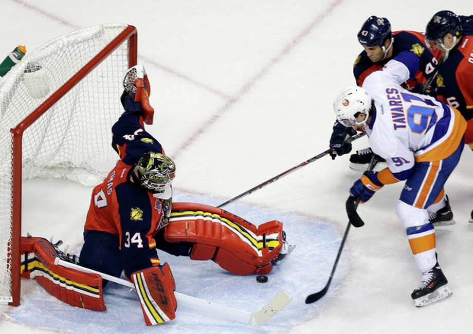 Florida Panthers goalie Tim Thomas (34) stops the puck as New York Islanders' John Tavares (91) attempts a shot on the goal during the second period of an NHL hockey game, Tuesday, Jan. 14, 2014, in Sunrise, Fla. (AP Photo/Lynne Sladky) / AP