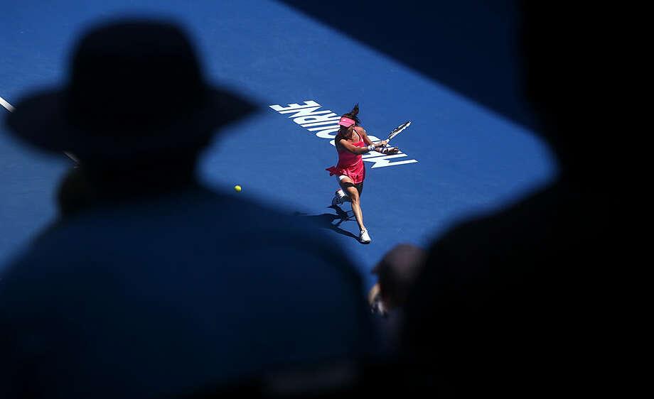 Agnieszka Radwanska of Poland plays a backhand return to Carla Suarez Navarro of Spain during their quarterfinal match at the Australian Open tennis championships in Melbourne, Australia, Tuesday, Jan. 26, 2016.(AP Photo/Rafiq Maqbool)