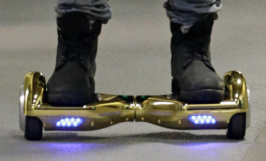 "In this Oct. 5, 2015, file photo, Seattle Seahawks wide receiver B.J. Daniels rides through a hallway at CenturyLink Field on an electric self-balancing scooter commonly called a ""hoverboard"" as he arrives for an NFL football game against the Detroit Lions in Seattle."