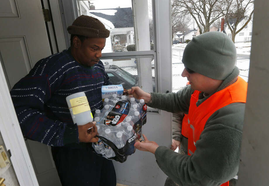 Louis Singleton receives water filters, bottled water and a test kit from Michigan National Guard Specialist Joe Weaver as clean water supplies are distributed to residents, Thursday, Jan. 21, 2016 in Flint, Mich. The National Guard, state employees, local authorities and volunteers have been distributing lead tests, filters and bottled water during the city's drinking water crisis. (AP Photo/Paul Sancya)