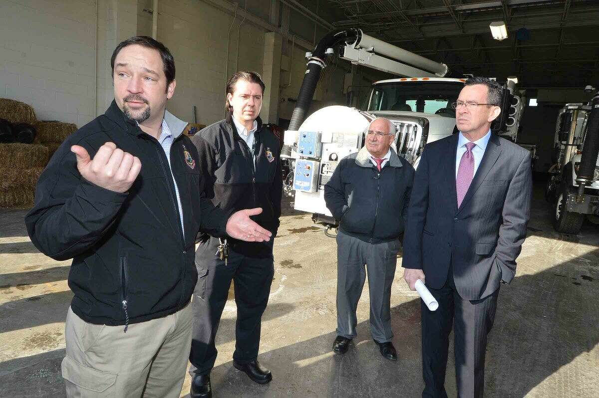 Tyler Theder, regulatory compliance and administrative officer with the city of Stamford's Office of Operations, talks with Gov. Dannel P. Malloy, Ernie Orgera, the city's director of operations and Thomas Turk, transportation and road maintenance supervisor, about two new vehicles the city recently purchased:A vactor truck, used to clean catch basins, and a CCTV camera truck, which provides live video feeds from underground pipes and basins.
