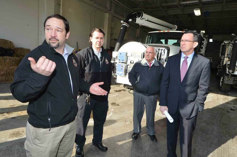 Tyler Theder, regulatory compliance and administrative officer with the city of Stamford's Office of Operations, talks with Gov. Dannel P. Malloy, Ernie Orgera, the city's director of operations and Thomas Turk, transportation and road maintenance supervisor, about two new vehicles the city recently purchased: A vactor truck, used to clean catch basins, and a CCTV camera truck, which provides live video feeds from underground pipes and basins.