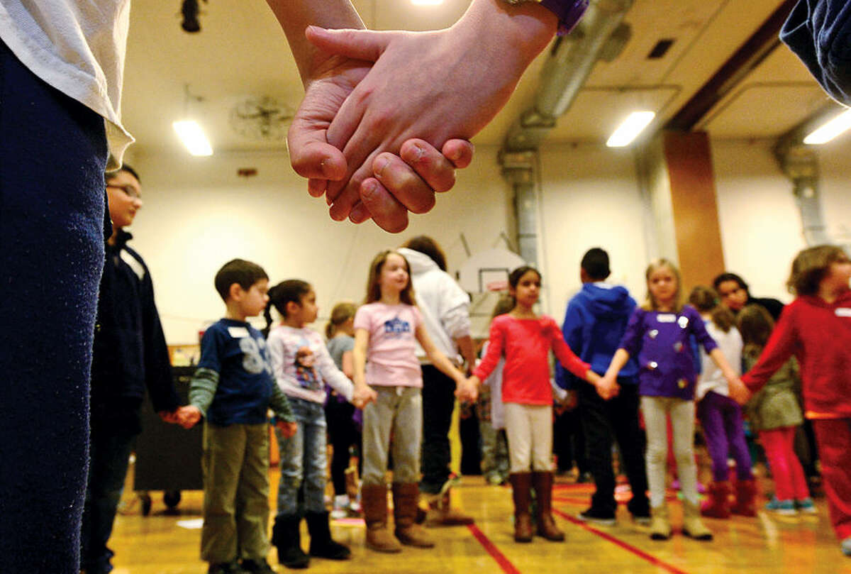 Hour photo / Erik Trautmann Columbus Magnet School students particpate in the school's annual Peace Games Friday during a special assembly with the theme, These Hands, to honor the work and memory of Dr. Martin Luther King, Jr.
