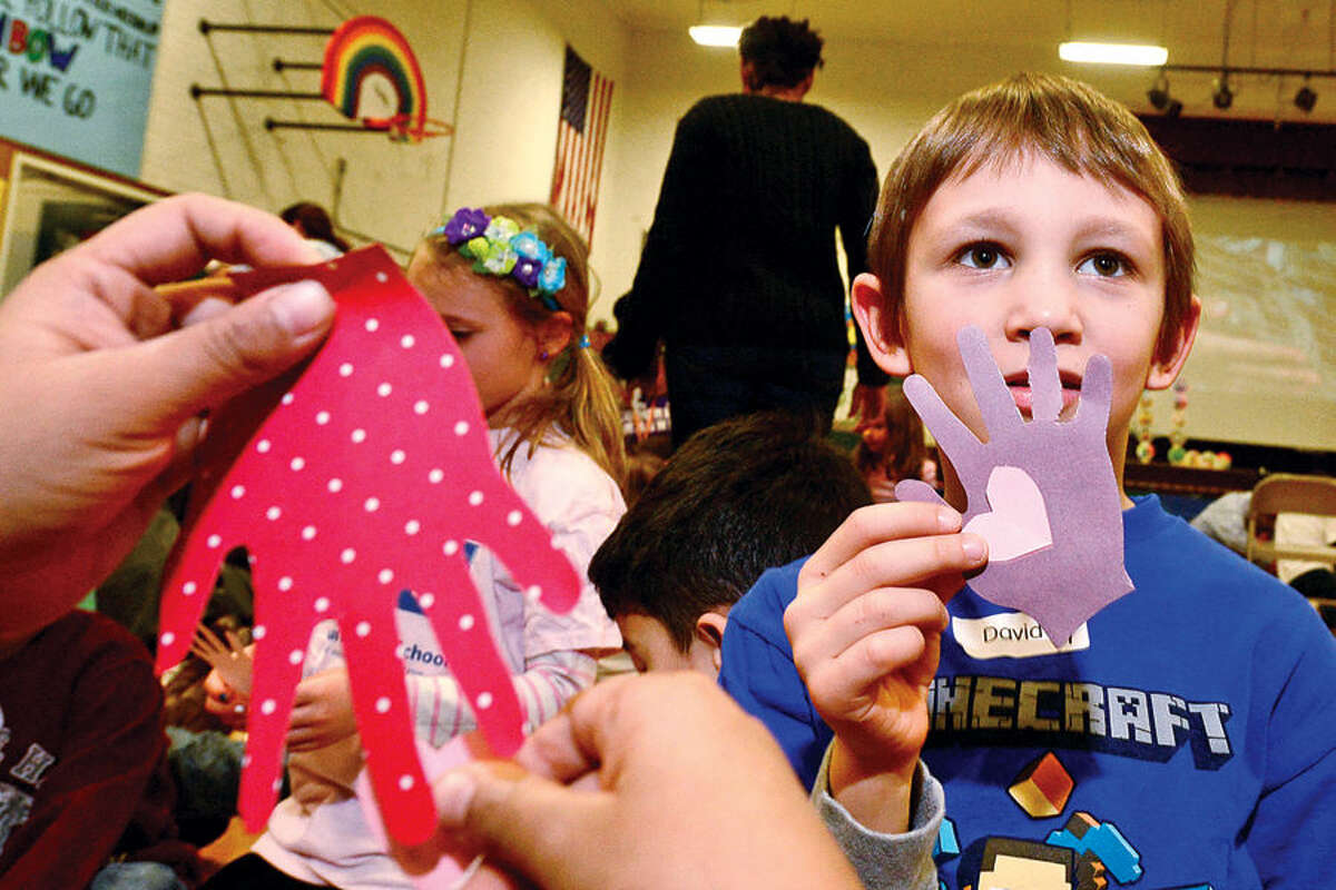 Hour photo / Erik Trautmann Columbus Magnet School studenst including first grader David Delong particpate in the school's annual Peace Games Friday during a special assembly with the theme, These Hands, to honor the work and memory of Dr. Martin Luther King, Jr.