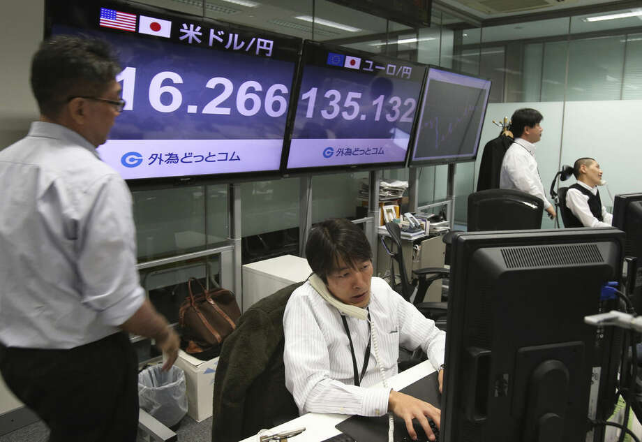 Money traders work in front of screens indicating the U.S. dollar is traded at 116.266 yen while the euro is at 135,132 yen at a foreign exchange brokerage in Tokyo Friday, Jan. 16, 2015. Asian stocks were sharply lower Friday after a surprise move by the Swiss National Bank to abandon its efforts to keep its currency artificially cheap shocked the market. Japan's Nikkei 225 dropped 2.8 percent to 16,628.06 while South Korea's Kospi fell 1.2 percent to 1,891.04. The dollar fell to 115.983 yen from 116.207 yen while the euro rose to $1.1634 from $1.1619. (AP Photo/Koji Sasahara)