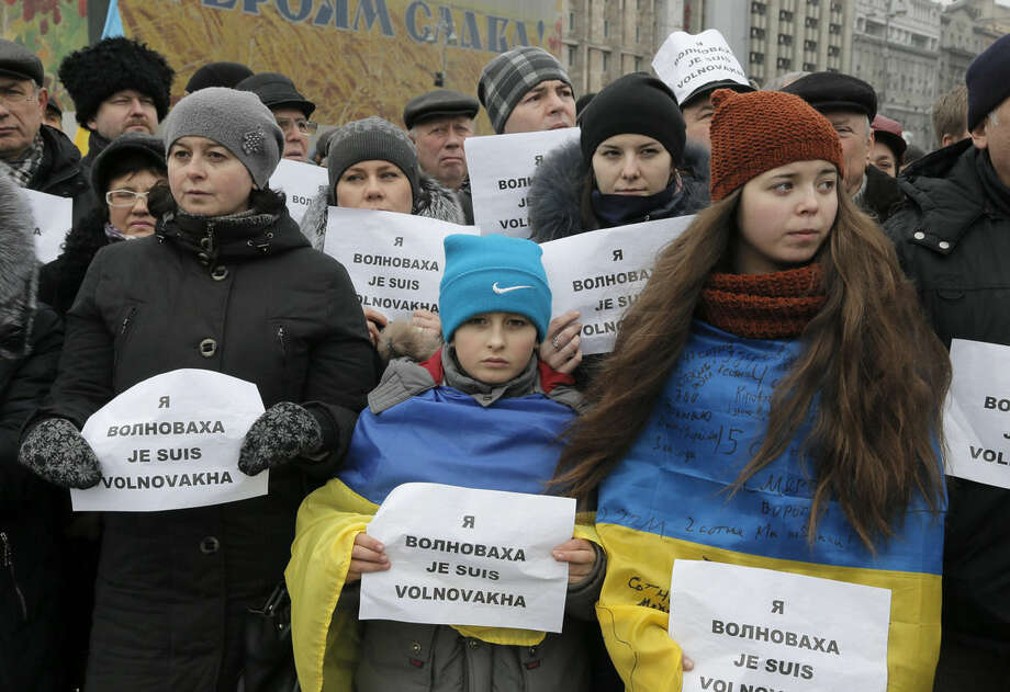 People hold signs that read: 'I am Volnovakha' during a rally on Independence Square in Kiev, Ukraine, in solidarity with the victims of a rocket attack this week that claimed 13 lives on a highway near the eastern town of Volnovakha, on Sunday, Jan. 18, 2015. Ukraine's government accuses Russian-backed separatists of launching the rocket attack, which hit a passenger bus, but the rebels have rejected that charge. (AP Photo/Efrem Lukatsky)