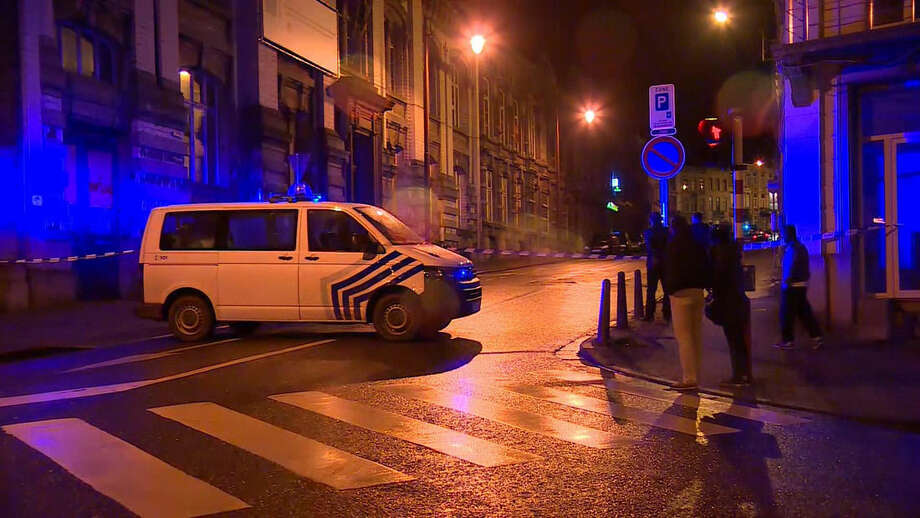 In this image made from video, members of the public stand behind police tape after security forces took part in anti-terrorist raids in Verviers, eastern Belgium. Belgian authorities say two people have been killed and one has been arrested during a shootout in an anti-terrorist operation in the eastern city of Verviers. (AP Photo/RTL - TVI) BELGIUM OUT