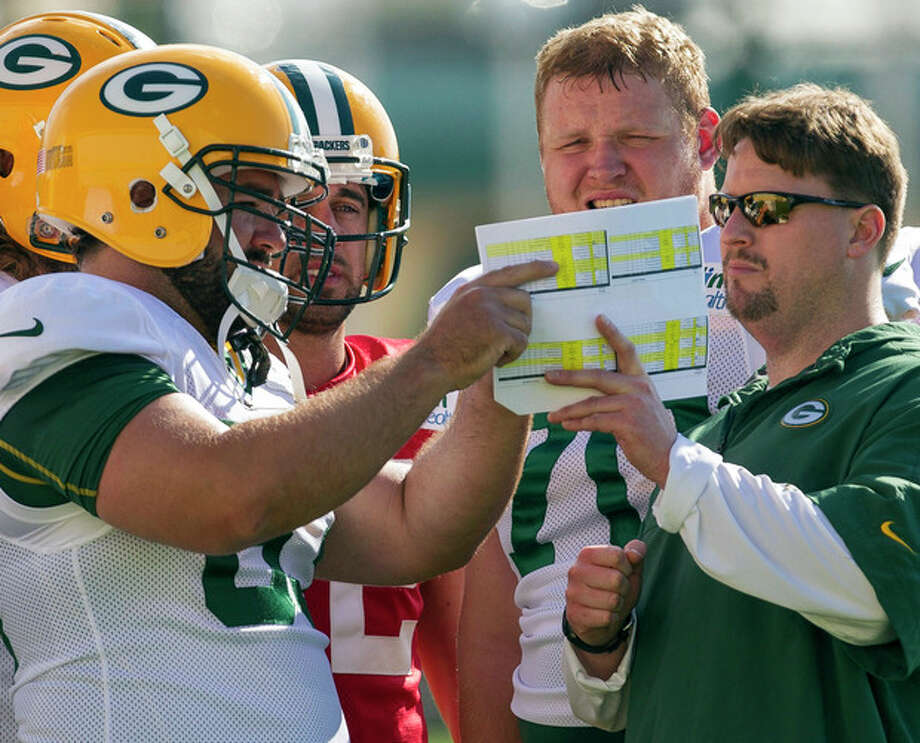 FILE - in this July 28, 2012, file photo, Green Bay Packers quarterbacks coach Ben McAdoo, right, center Jeff Saturday (63), quarterback Aaron Rodgers (12) and offensive guard T.J. Lang (70) talk during NFL football training camp in Green Bay, Wis. The New York Giants on Tuesday, Jan. 14, 2014, hired McAdoo as their new offensive coordinator. (AP Photo/Mike Roemer, File) / FR155603 AP
