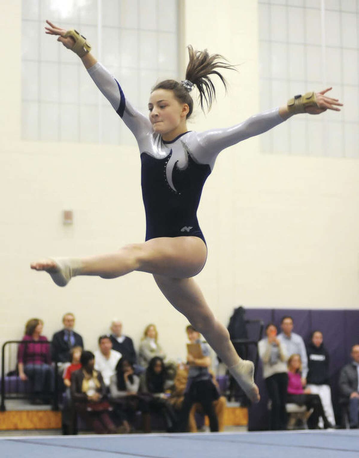 Hour photo/John Nash Staples sophomore Eliza Donovan leaps through air during her floor exercise at Wednesday's tri-meet against Westhill and New Canaan in Stamford.