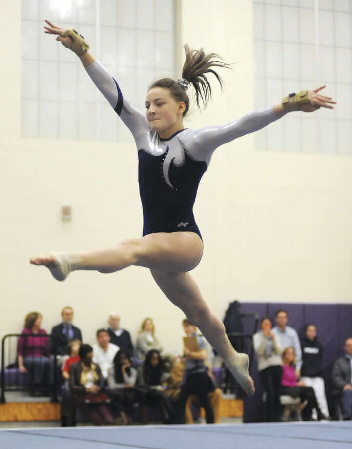 Hour photo/John NashStaples sophomore Eliza Donovan leaps through air during her floor exercise at Wednesday's tri-meet against Westhill and New Canaan in Stamford.