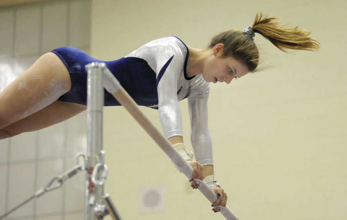 Hour photo/John Nash Staples' Anna Violette gets a view from the higher of the uneven bars during Wednesday's FCIAC tri-meet against Westhill and New Canaan in Stamford.