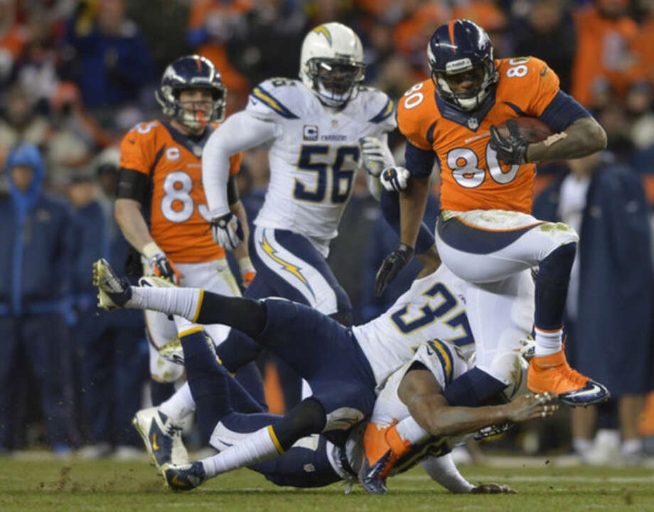 Denver Broncos tight end Julius Thomas (80) is tackled by San Diego Chargers strong safety Marcus Gilchrist (38) and San Diego Chargers defensive back Jahleel Addae (37) in the fourth quarter of an NFL AFC division playoff football game, Sunday, Jan. 12, 2014, in Denver. (AP Photo/Jack Dempsey)