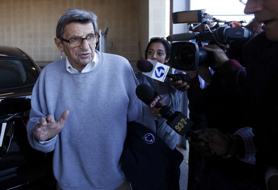 FILE - In this Nov. 8, 2011, file photo, Penn State football coach Joe Paterno speals with reporters as leaves the Louis and Mildred Lasch Football Building on campus in State College, Pa. A proposed settlement, announced Friday, Jan. 16, 2015, by the NCAA, will give Penn State back 112 football team wins that were vacated two years ago in the Jerry Sandusky child molestation scandal. If approved, the new agreement also would restore former coach Paterno's status as the winningest coach in major college football history with 409 victories. (AP Photo/Matt Rourke, File)