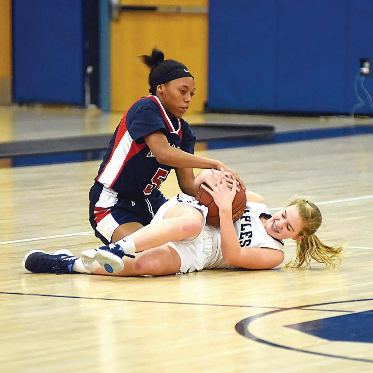 Hour photo/John Nash - Staples' Elle Fair, bottom, gets tied up by Brien McMahon's Aiyanna Lee-Williams during Friday's girls basketball game in Westport.