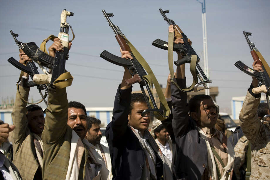 Houthi Shiite Yemeni raise their weapons during clashes near the presidential palace in Sanaa, Yemen, Monday, Jan. 19, 2015. Rebel Shiite Houthis battled soldiers near Yemen's presidential palace and elsewhere across the capital Monday, despite a claim of a cease-fire being reached to halt the violence, witnesses and officials said. (AP Photo/Hani Mohammed)