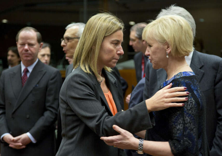 European Union High Representative Federica Mogherini, center, speaks with Swedish Foreign Minister Margot Wallstrom, right, during a meeting of EU foreign ministers in Brussels on Monday, Jan. 19, 2015. The European Union is calling for an anti-terror alliance with Arab countries to boost cooperation and information sharing in the wake of deadly attacks and arrests across Europe linked to foreign fighters. (AP Photo/Virginia Mayo)
