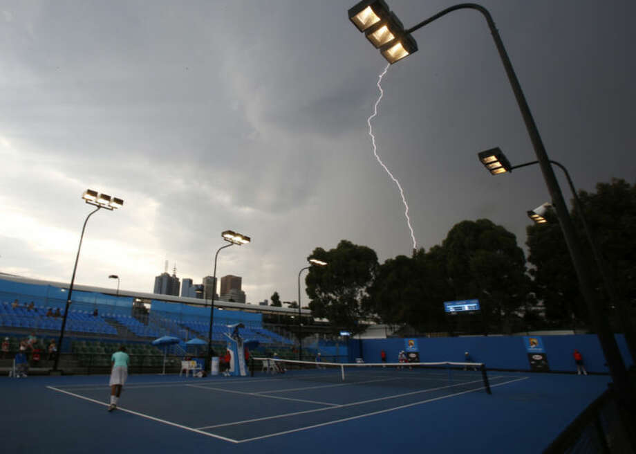 The lightning is seen in the sky at an outside court at the Australian Open tennis championship in Melbourne, Australia, Thursday, Jan. 16, 2014.(AP Photo/Shuji Kajiyama)