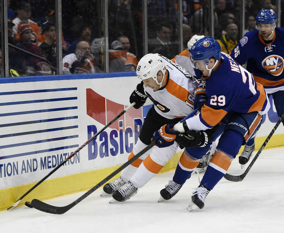Philadelphia Flyers left wing R.J. Umberger (18) and New York Islanders center Brock Nelson (29) battle for the puck in the first period of an NHL hockey game at Nassau Coliseum on Monday, Jan. 19, 2015, in Uniondale, N.Y. (AP Photo/Kathy Kmonicek)