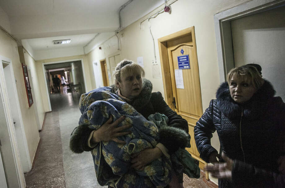 A woman holds a child in the basement of Hospital Nº 3, after it was hit by Ukrainian Army artillery in Kalininsky district, in Donetsk, Ukraine. Monday, Jan. 19, 2015. The separatist stronghold, Donetsk, was shaken by intense outgoing and incoming artillery fire on Sunday as a bitter battle raged for control over the city's airport. Streets in the city, which was home to 1 million people before unrest erupted in spring, were completely deserted and the windows of apartments in the center rattled from incessant rocket and mortar fire. (AP Photo/Manu Brabo)
