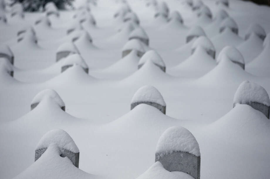 FILE - In this Jan. 23, 2016, file photo, headstones are nearly covered by snow at Arlington National Cemetery in Arlington, Va. The National Oceanic and Atmospheric Administration said Thursday, Jan. 28, 2016, that last week's blizzard was the fourth most powerful snowstorm to hit the Northeast in at least 60 years. (AP Photo/Alex Brandon, File)