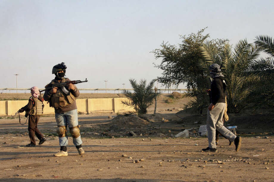 In this Wednesday, Jan. 15, 2014 photo, gunmen hold their weapons as they patrol Fallujah, 65 kilometers (40 miles) west of Baghdad, Iraq. Iraqi airstrikes pounded a town near Fallujah that had been seized by al-Qaida linked militants and commandos swept in Wednesday to clear the area, senior military officials said. It was a rare victory for government forces that have been struggling for nearly three weeks to regain control of the mainly Sunni area west of Baghdad. (AP Photo)