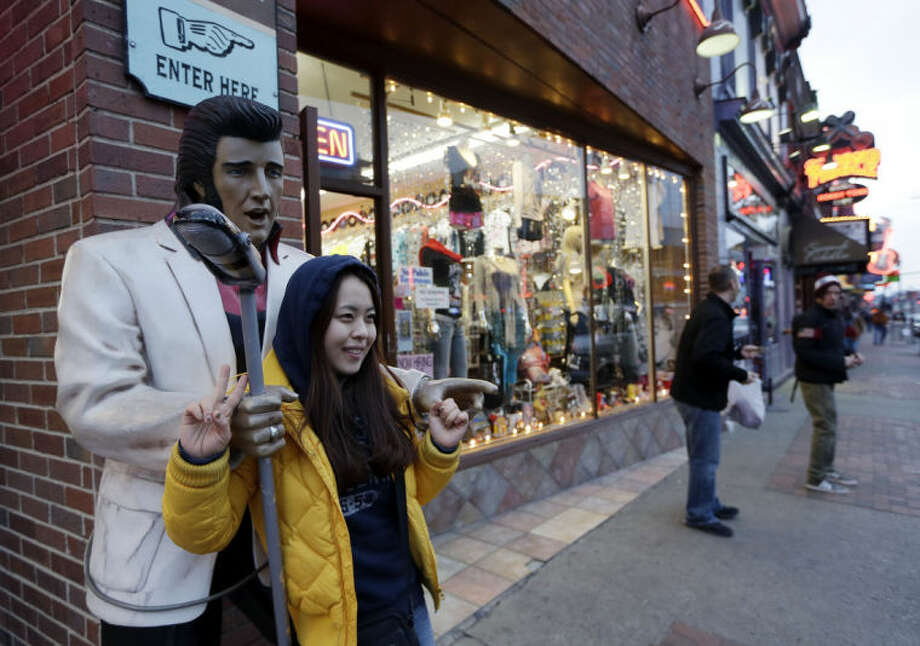 This Jan. 15, 2014 photo shows Kim Young, of Seoul, South Korea, posing for a photo by a statue of Elvis Presley while visiting Broadway in Nashville, Tenn. Broadway is lined with honky tonks, restaurants and souvenir shops.(AP Photo/Mark Humphrey)