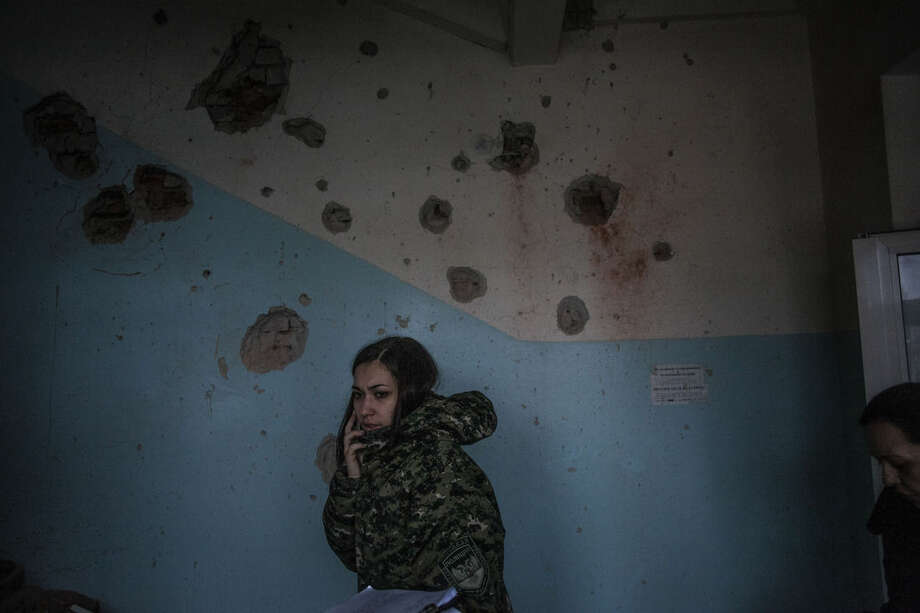 A female DNR officer talks on the phone in Hospital Nº 3, after it was hit by Ukrainian Army artillery in Kalininsky district, in Donetsk, Ukraine. Monday, Jan. 19, 2015. The separatist stronghold, Donetsk, was shaken by intense outgoing and incoming artillery fire on Sunday as a bitter battle raged for control over the city's airport. Streets in the city, which was home to 1 million people before unrest erupted in spring, were completely deserted and the windows of apartments in the center rattled from incessant rocket and mortar fire. (AP Photo/Manu Brabo)