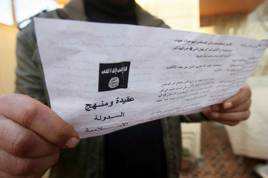 A man reads a pamphlet issued by al-Qaida-linked militants in Fallujah, Iraq, Thursday, Jan. 16, 2014. Members of al-Qaida's local franchise handed out pamphlets urging residents in the western city of Fallujah to take up arms and back the militants in their weeks-long fight against Iraqi troops as clashes raged on around the city, residents said Thursday. (AP Photo)