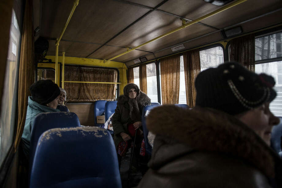 An elderly Ukrainian woman sits on a bus after being evacuated from Hospital Nº 3, after it was hit by Ukrainian Army artillery in Kalininsky district, in Donetsk, Ukraine. Monday, Jan. 19, 2015. The separatist stronghold, Donetsk, was shaken by intense outgoing and incoming artillery fire on Sunday as a bitter battle raged for control over the city's airport. Streets in the city, which was home to 1 million people before unrest erupted in spring, were completely deserted and the windows of apartments in the center rattled from incessant rocket and mortar fire. (AP Photo/Manu Brabo)