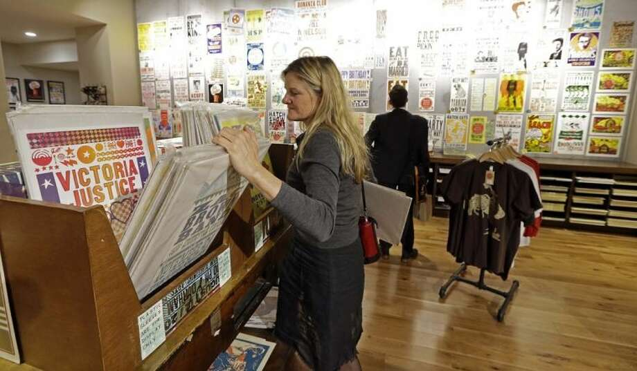 This Jan. 15, 2014 photo shows Ellen Kuras, of New York, looking through posters at the Hatch Show Print shop in Nashville, Tenn. Besides being able to buy unique posters, there's no cost to watch the presses and the staff churn out the iconic handmade art that has been used by everyone from Grand Ole Opry stars to blues and jazz greats and modern rock bands. (AP Photo/Mark Humphrey)