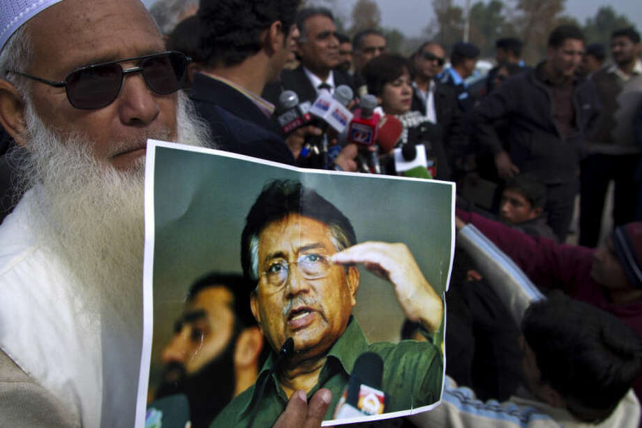A supporter of Pakistan's former president and military ruler Pervez Musharraf holds a poster with a photo of him during a news conference with Musharraf's lawyers outside the special court in Islamabad, Pakistan, Thursday, Jan. 16, 2014. A lawyer for Musharraf who is on trial for high treason said his client has been advised to go to the U.S. for medical treatment. (AP Photo/B.K. Bangash)