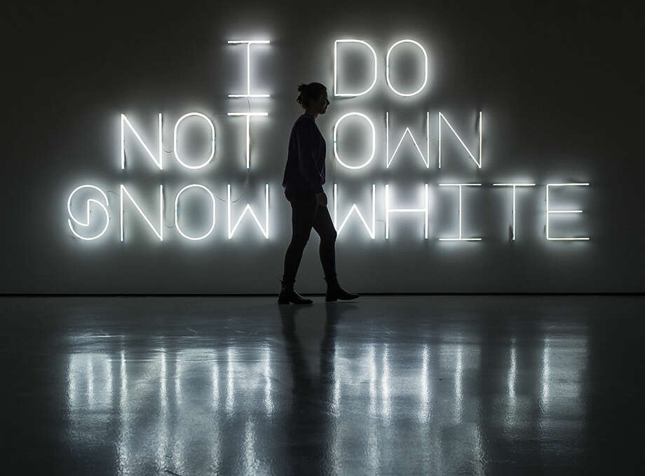 A woman walks in front of the installation 'I do not own snow white' (2005, neon tubes) by French artist Pierre Huyghe during the press preview at the exhibition 'Images' in the Fridericianum in Kassel, Germany, Friday, Jan. 29, 2016. The works presented in this exhibition explore the image at the moment of its fundamental reconfiguration. The exhibition starts on Jan. 31, 2016 and lasts until May 1, 2016. (AP Photo/Jens Meyer)