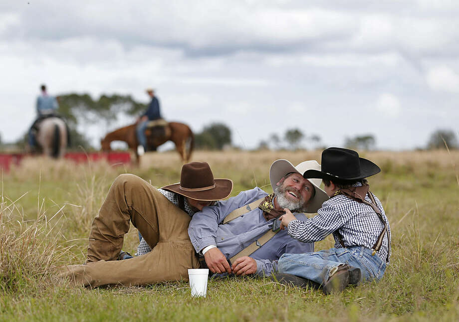 In this Tuesday, Jan. 26, 2016 photo, Richard Claybrooke, center, of Parrish, Fla., sits with his sons Brady, left, 7, and Logan, 10, after stopping for lunch during the Great Florida Cattle Drive 2016, in Kenansville, Fla. The once-a-decade event was organized to draw attention to Florida's deep cowboy history. (AP Photo/Wilfredo Lee)