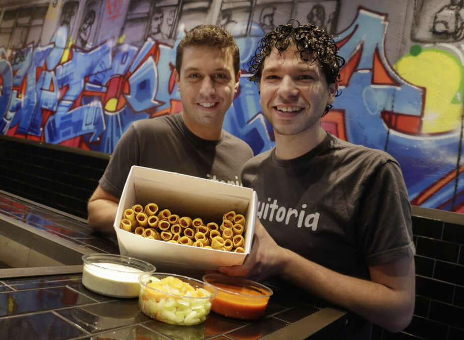 Culinary Director Barry Frish, left, and owner and manager Brad Holtzman of Taquitoria, on New York's Lower East Side, pose with a box of Buffalo chicken taquitos, Tuesday, Jan. 14, 2014. Taquitoria, a shop that serves only the deep-fried, cigar-like tortillas called taquitos, offers 40-piece boxes of the Buffalo chicken taquitos throughout football season. On Super Bowl game day they expect to do 99 percent of their business for takeout. (AP Photo/Richard Drew)