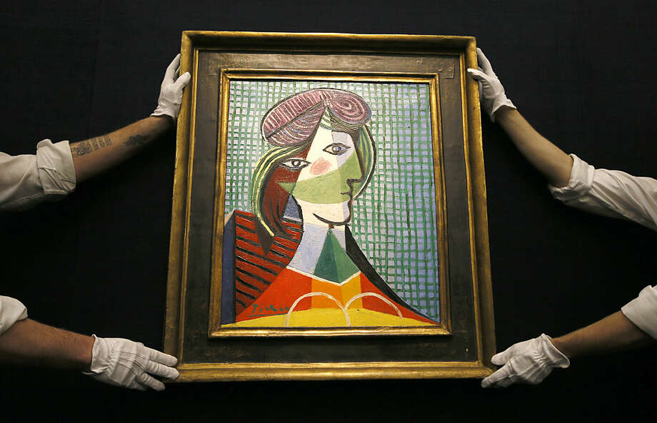 Sotheby's employees adjust a painting by Pablo Picasso called 'Tete de Femme' at the auction rooms in London, Thursday, Jan. 28, 2016. The painting is estimated at 16-20 million pounds (US$23-29 million) when it goes up for auction in London on Feb. 3. in the Impressionist and Modern Art Evening Sale. (AP Photo/Kirsty Wigglesworth)