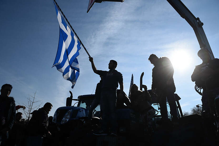 A protesting farmer waves a Greek flag during a rally in the northern Greek city of Thessaloniki on Thursday, Jan. 28, 2016. Greek farmers continued highway blockades as a range of other professions are on strike to protest planned pension reforms that are part of the country's third international bailout requirements. (AP Photo/Giannis Papanikos)